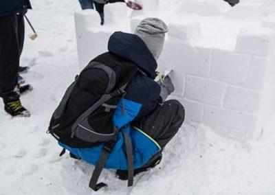 Lumenveistokisassa opiskelija veistää lumesta linnaa.