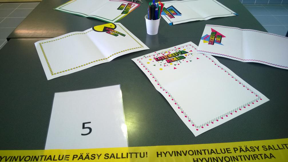 """Pöydällä monisteita, joissa Liikkuva amis -logo. Papereihin voi kirjoittaa ideoita. Papereiden välissä teline, jossa erilaisia kyniä. Pöydän päällä teippi, jossa lukee """"Hyvinvointi alue pääsy sallittu""""."""