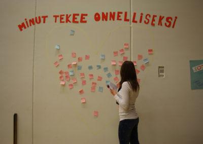 """Opiskelija liimaa seinälle post it -lappua useiden muiden lappujen sekaan. Seinällä lukee suurella lappujen keskellä """"minut tekee onnelliseksi""""."""