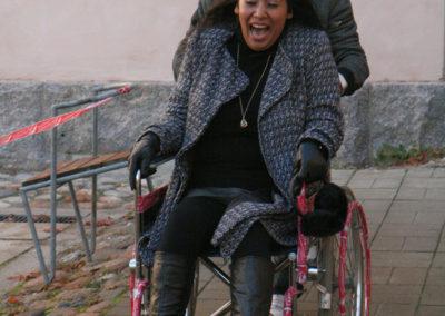 Kaksi henkilöä ulkona. Toinen työntää toista pyörätuolissa vauhdikkaasti.