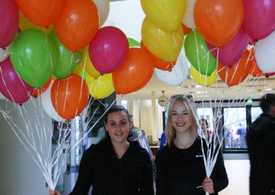Kaksi opiskelijaa ilmapallokimppujen kanssa oppilaitoksen aulassa.
