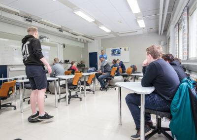 Opiskelijat luokkahuoneessa. Kaksi istuu jumppapallolla ja etualalla yksi seisoo tasapainolaudalla.