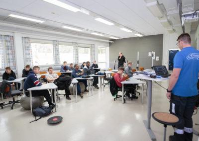 Luokkahuoneessa oppilaita. Kaksi istuu jumppapallolla. Lattialla on tasapainolauta.
