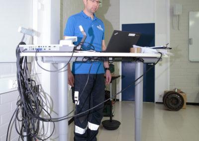 Opettaja käyttää työpisteenä seisomapöytää ja seisoo tasapainolaudalla.