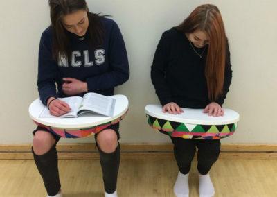 Kaksi opiskelijaa nojaa seinään istuma-asennossa ilman tuolia. Sylissä lukualusta kirjaa varten.