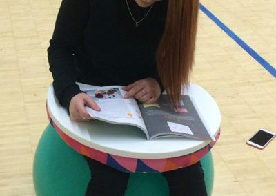 Opiskelija lukee kirjaa lukualustaa käyttäen ja istuen jumppapallolla.