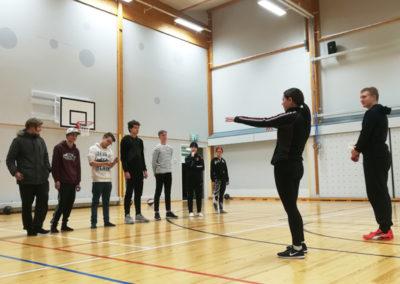Opiskelijoita liikuntasalissa. Seitsemän seisoo rivissä. Kaksi toisella puolella osoittamassa.