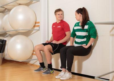 Kaksi opiskelijaa istuu seinää vasten liikuntasalissa. Vieressä jumppapalloja.