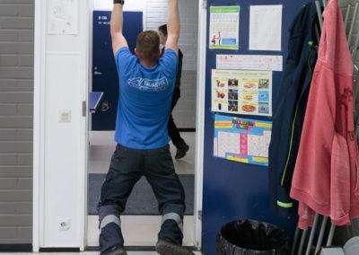 Opiskelija roikkuu työvaatteissa ovenväliiin kiinnitetyssä leuanvetotangossa.
