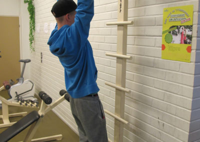 Opiskelija roikkuu käsillään telineessä jalat ilmassa.