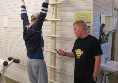 Opiskelija roikkuu käsillään telineestä jalat ilmassa. Toinen opiskelija tarkkailee puhelimen kädessä.