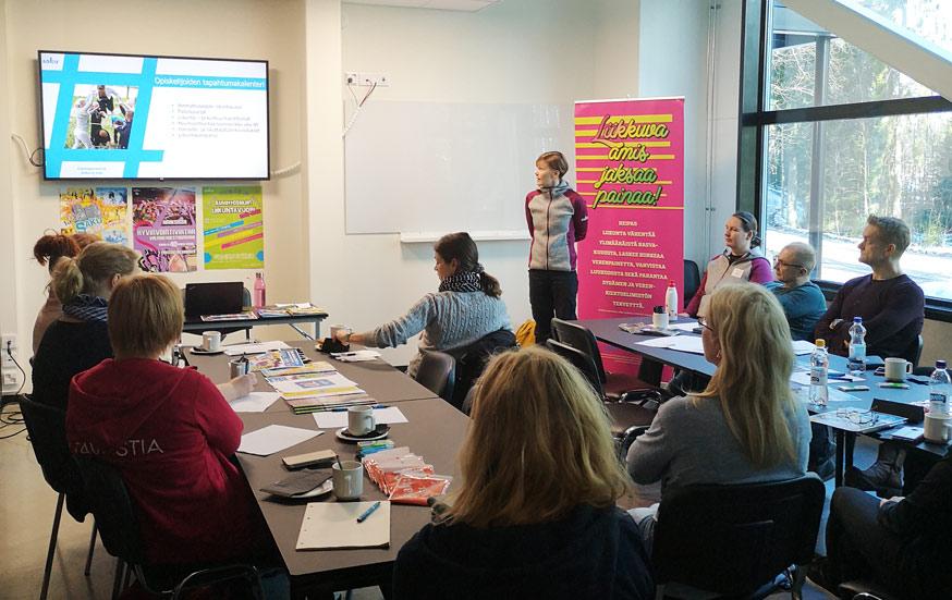 Yksitoista henkilöä kokoontunut kuuntelemaan luentoa luokkahuoneeseen. Luentoa pitää SAKU ry:n työntekijä. Taustalla Liikkuva amis -rollup.