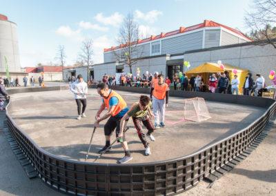 Opiskelijat pelaamassa katusäbää asfaltille rakennetussa kaukalossa.