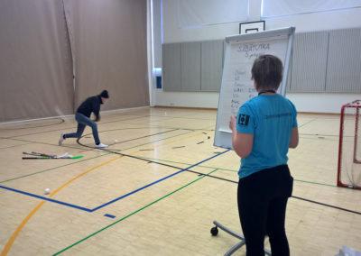 Liikuntasalissa säbätutka. Opiskelija lämää sählymailalla viivalta palloa tyhjään maaliin. Toinen henkilö merkitsee fläppitauluun tilastoja.