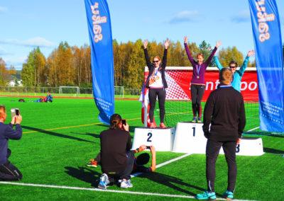 Kolme henkilöä tuulettaa palkintopallilla urheilukentällä. Neljä henkilö kuvaa kännyköillä..