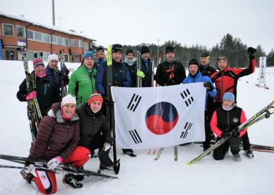 Viisitoista hiihtäjää poseeraa sukset kainalossa maalialueella. Taustalla lukee FINISH. Etualalla Etelä-Korean lippu mahdollisesti vahingossa väärinpäin.