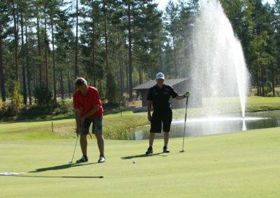 Kaksi henkilöä golf-kentällä. Toinen puttaa ja toinen katselee taustalla. Golf-kentän reunassa vesieste, jossa suihkulähde. Taustalla metsä.