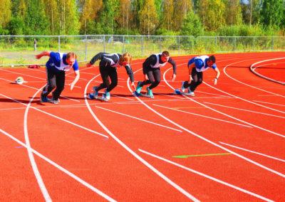 Neljä henkilöä starttaa juoksuun lähtötelineistä urheilukentän juoksuradalla.