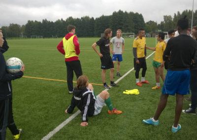 Opiskelijoita jalkapallokentän laidalla valmistautumassa pelaamaan jalkapalloa.