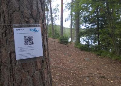 Oppilaitossuunnistuksen rasti kiinnitettynä puuhun. Rastissa tekstiä ja QR-koodi.