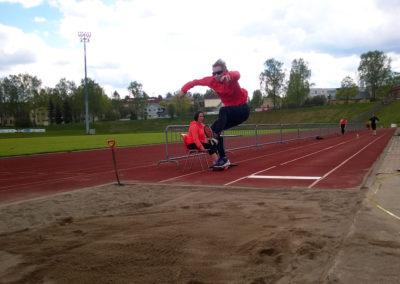 Henkilö hyppäämässä pituutta urheilukentän pituushyppypaikalla.