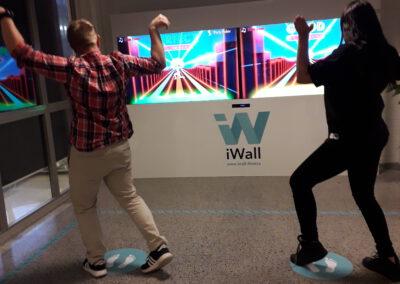 Kaksi opiskelijaa pelaa iWall-peliä oppilatoksen aulassa.
