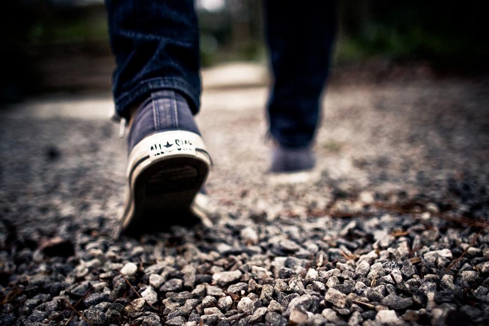 Jalat kävelevät soratiellä